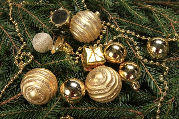 High angle shot of golden baubles with string beads on fir branches