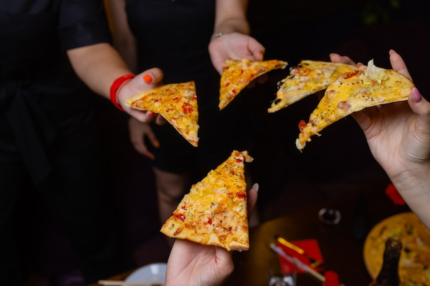 High angle shot of a group of unrecognizable people's hands each grabbing a slice of pizza.