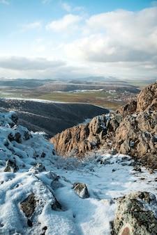 Colpo ad alto angolo delle montagne di alta collina coperte di poca neve durante il giorno