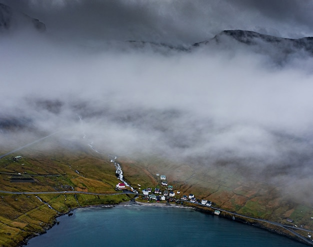 High angle shot of houses on a grass-covered hill by the water captured on a foggy evening