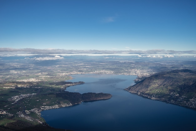 Colpo di alto angolo del lago di zugo in svizzera sotto un cielo blu chiaro