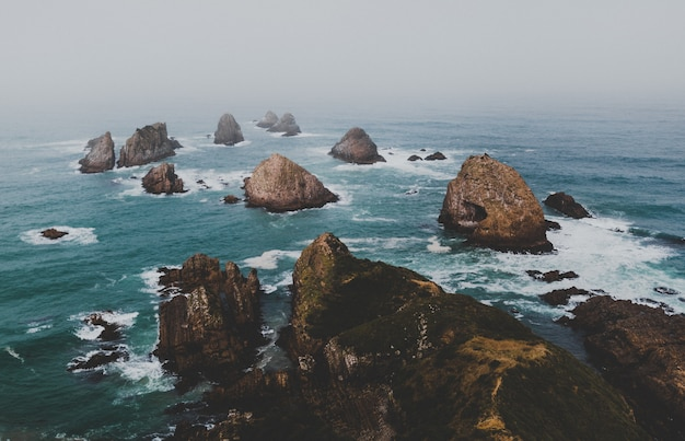 High angle shot of large rocks in nugget point ahuriri, new zealand with a foggy background
