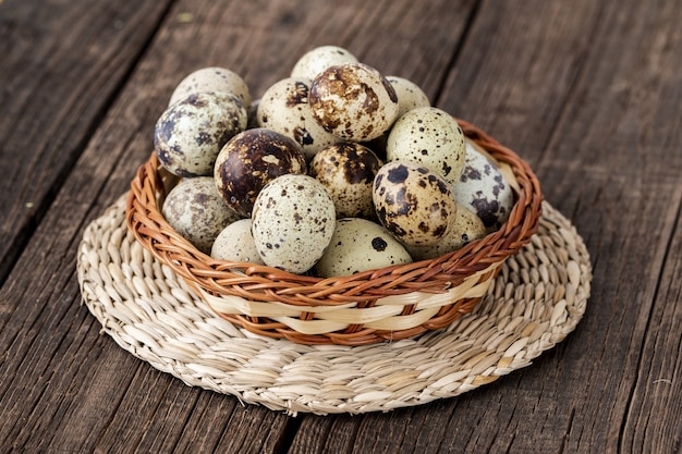 High angle shot of many quail eggs in a woven basket on a wooden table