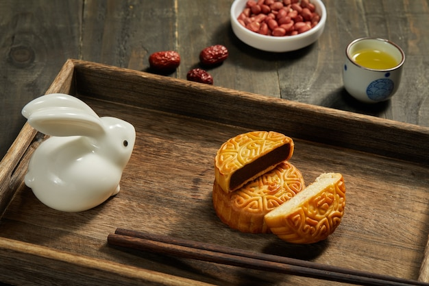 High angle shot of mooncakes with chopsticks on a wooden tray