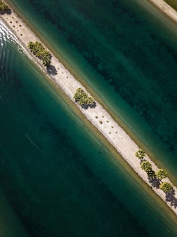 High angle shot of a narrow sand line with green trees in the middle of the sea
