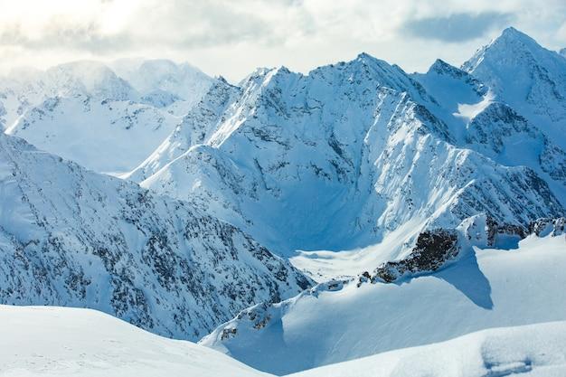 흐린 하늘 아래 눈으로 덮여 아름다운 산맥의 높은 각도 샷