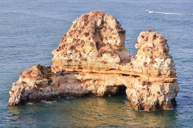 Снимок красивой скалы посреди моря под высоким углом
