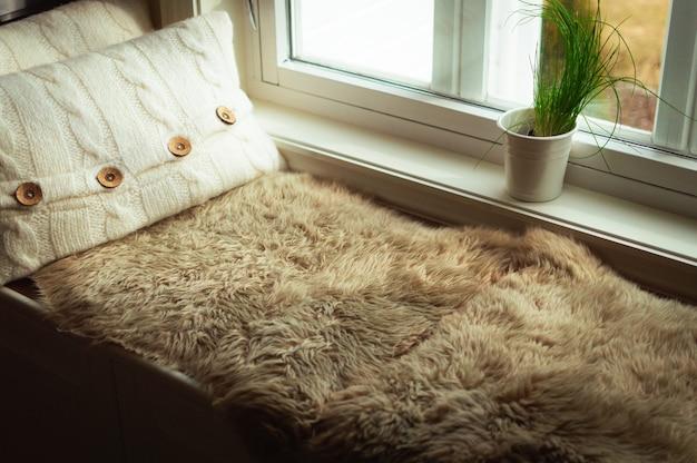 Снимок кровати, подушек у окна и вазы под высоким углом на мадейре, португалия.