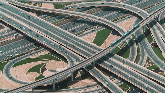Снимок большого шоссе с множеством дорог и поезда, едущего по центральной дороге, под высоким углом.
