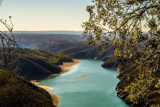 나무로 덮인 언덕으로 둘러싸인 큰 강의 높은 각도 샷
