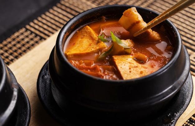 나무 테이블에 맛있는 고기와 야채 수프 그릇의 높은 각도 샷