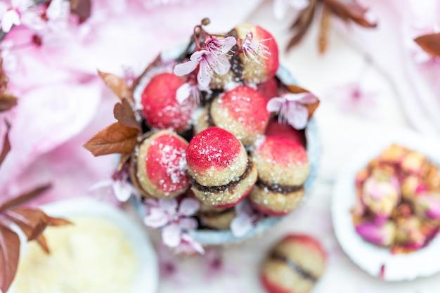 小さな花に囲まれたおいしいビーガンピーチクッキーのボウルのハイアングルショット
