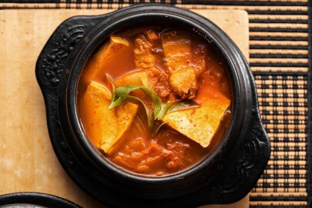 木製のテーブルの上においしい野菜とジャガイモのスープのボウルのハイアングルショット