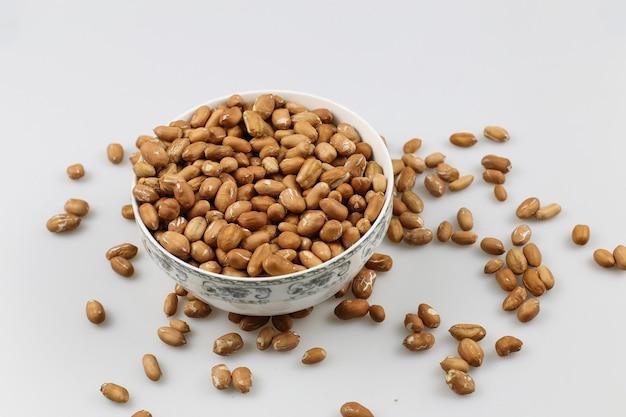 Снимок миски с арахисом на белой поверхности под высоким углом