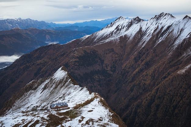 曇り空の下で雪に覆われた山の上にある建物のハイアングルショット