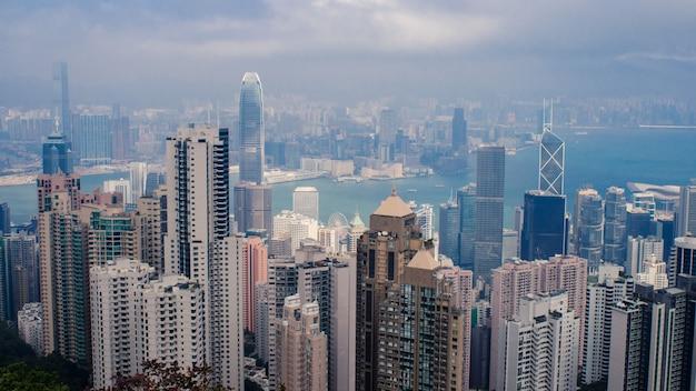 香港の曇り空の下で背の高い高層ビルがたくさんある街並みのハイアングルショット