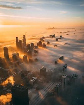 흰 구름으로 덮여 일몰 동안 높이 마천루와 도시의 높은 각도 샷