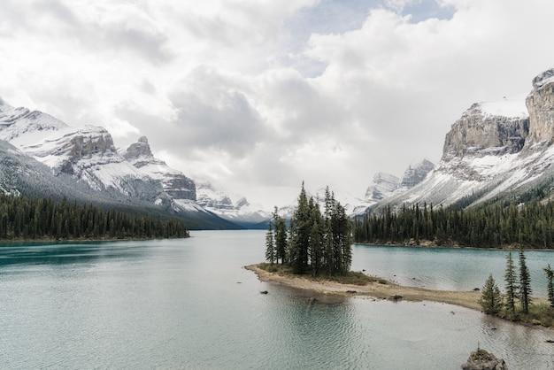 산악 풍경으로 둘러싸인 맑은 얼어 붙은 호수의 높은 각도 샷