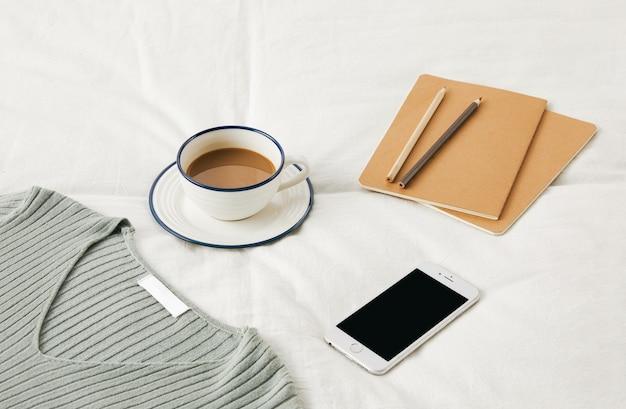 스케치북, 전화 및 스웨터가있는 침대 시트에 커피 한 잔의 높은 각도 샷