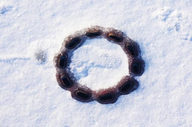 雪の降る地面の排水溝のハイアングルショット