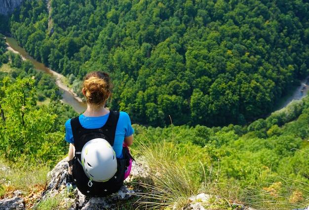 森を見下ろす崖の端に座っている女性ハイカーのハイアングルショット