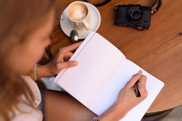ノートに書き込み、コーヒーを飲む女性のハイアングルショット