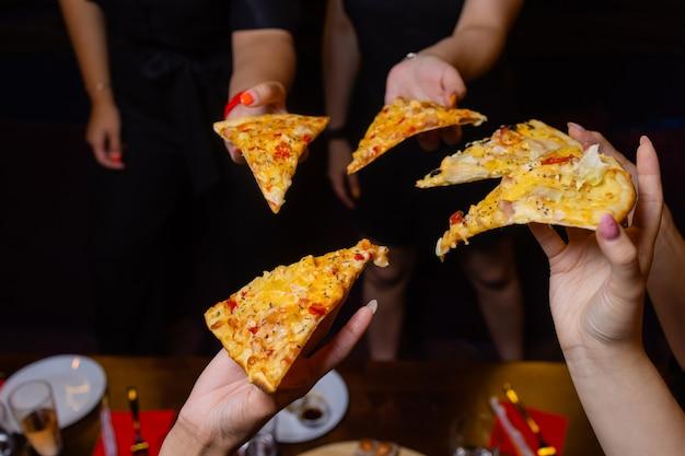 認識できない人々の手のグループがそれぞれピザのスライスをつかんでいるハイアングルショット。