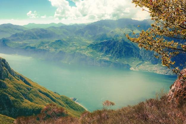 Снимок озера с высоким углом в окружении зеленых гор, покрытых туманом, под облачным небом