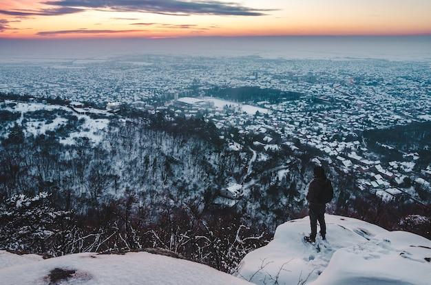 Снимок с высоким углом: мужчина стоит на заснеженной горе и любуется городом и закатом внизу.