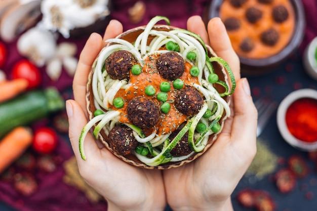 Снимок человека с миской вкусных овощных фрикаделек с высоким углом