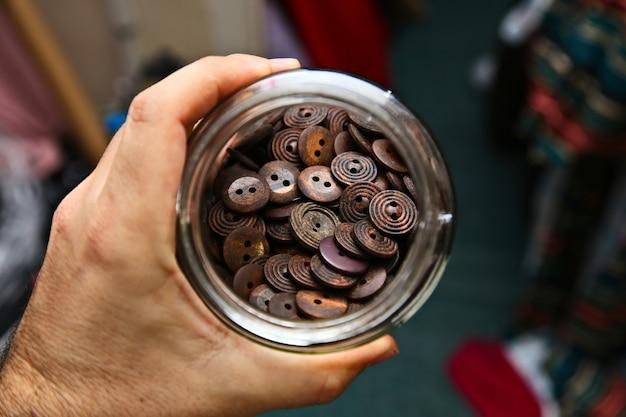 茶色のボタンでいっぱいの瓶を持っている人のハイアングルショット