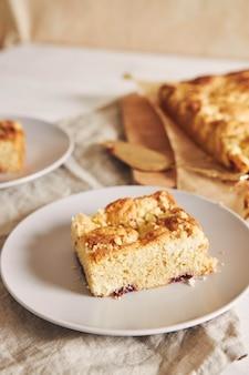 白い木のテーブルの上のおいしいジェリークランブルシートケーキのピースのハイアングルショット