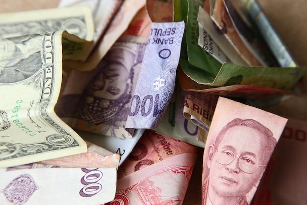 木製の表面にさまざまな国からの紙幣の山のハイアングルショット