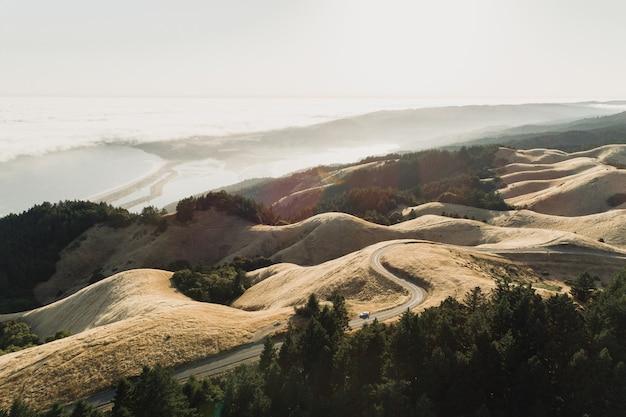 Снимок дороги посреди безлюдного пейзажа под высоким углом