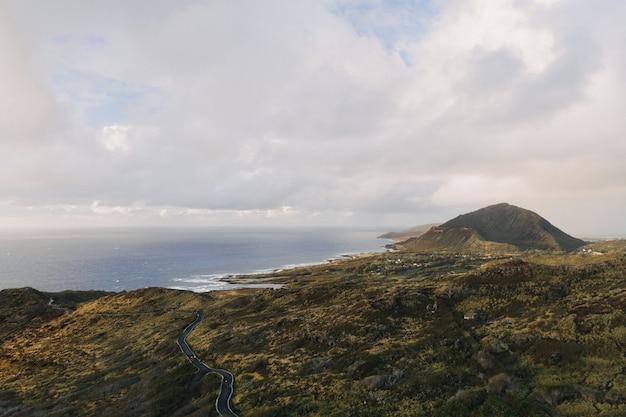 Снимок берега моря с высоким углом на фоне облачного голубого неба