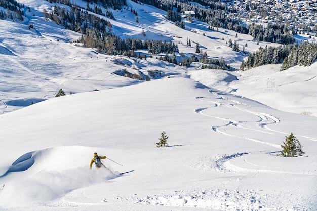 Панорамный снимок горнолыжного курорта с лыжными трассами и спускающегося по склону лыжника.