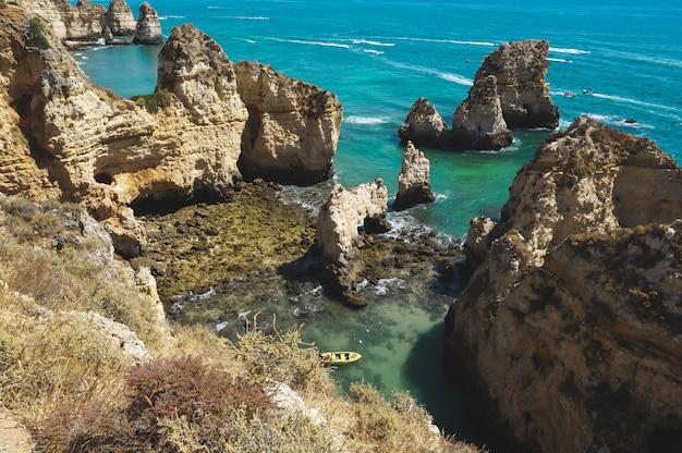Высокий угол выстрела маленькой лодке в лагуне, в окружении скал в океане