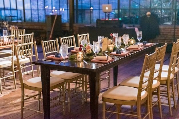 Панорамный снимок стола с элегантной обстановкой в зале ресторана вечером