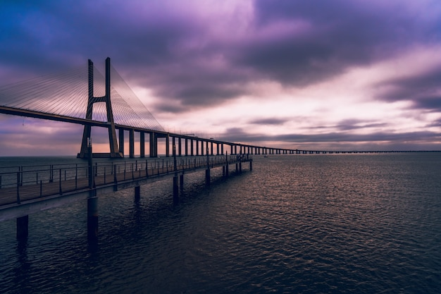 紫の空の下で海に架かる木製の橋のハイアングルショット