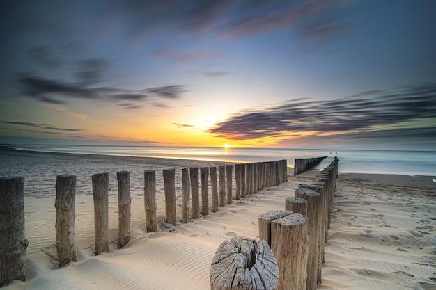 해질녘 바다로 이어지는 해변에 나무 갑판의 높은 각도 샷
