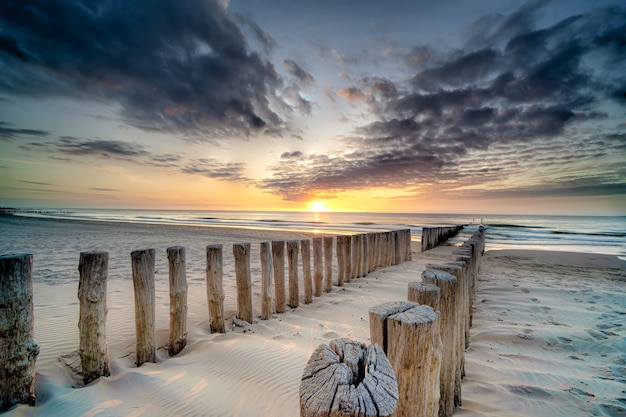 Снимок деревянной террасы на берегу, ведущей к морю на закате, под высоким углом