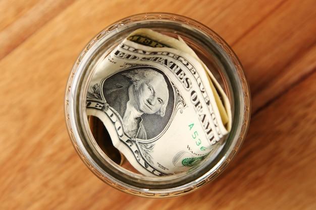 나무 표면에 유리 항아리에 미국 달러 지폐의 높은 각도 샷