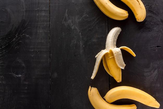 Снимок бананов под высоким углом с копией пространства на черном фоне