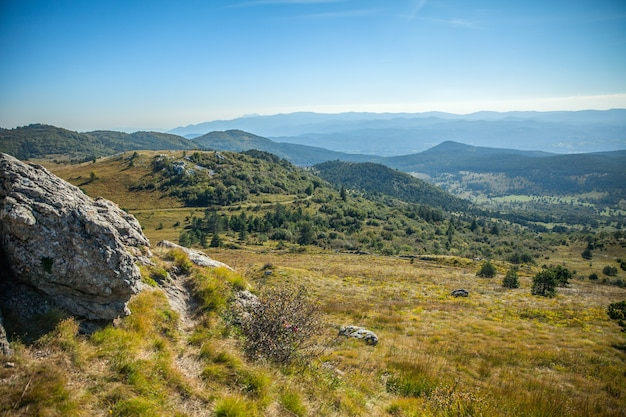 슬로베니아의 푸른 하늘 아래 숲과 아름다운 산의 높은 각도 샷