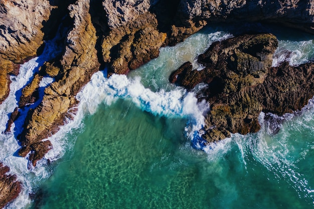 Высокий угол выстрела больших скал, покрытых морскими волнами в дневное время