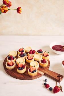 Снимок сырных кексов с мармеладом и фруктами на деревянной тарелке под высоким углом