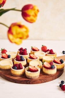 나무 접시에 과일 젤리와 과일 치즈 컵 케이크의 높은 각도 샷
