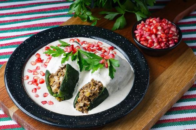 Снимок chiles en nogada с высоким углом в тарелке на деревянной доске на столе