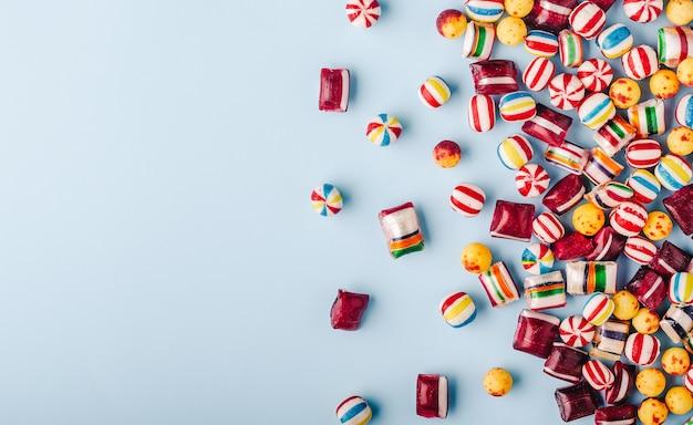 Снимок красочных конфет на голубом фоне под высоким углом