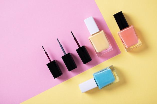 Снимок разноцветных лаков для ногтей на разноцветной бумаге под высоким углом